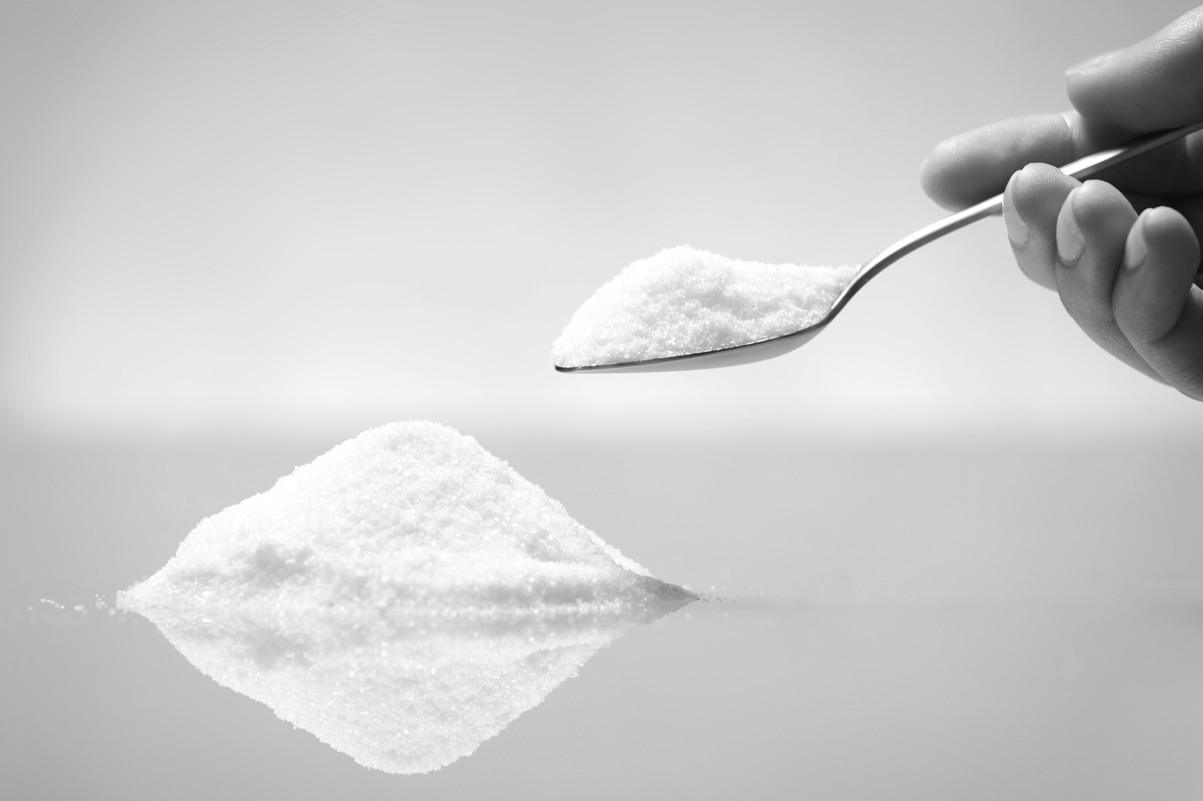Prelon Dichtsystem GmbH Krefeld - A pile of salt and a hand holding a silver spoon.
